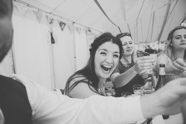 A funny and emotional image of a wedding guest at a tipi wedding in west wales cheers her friends ahead of drinking a shot when toasting the bride and groom.