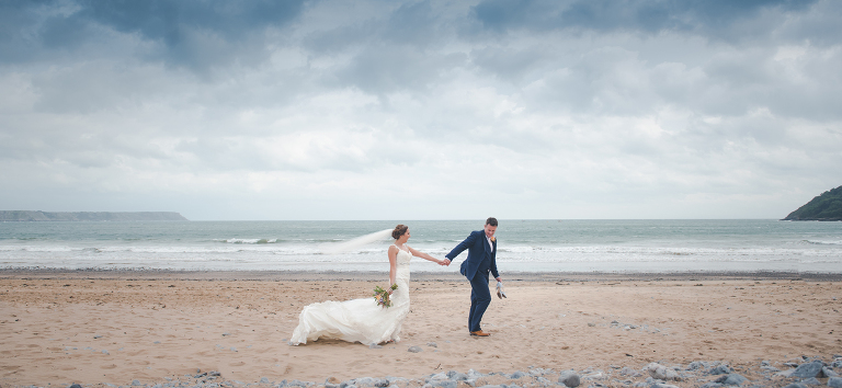 Image of couple strolling along Oxwich Bay beach hand in hand with a blue sky behind them