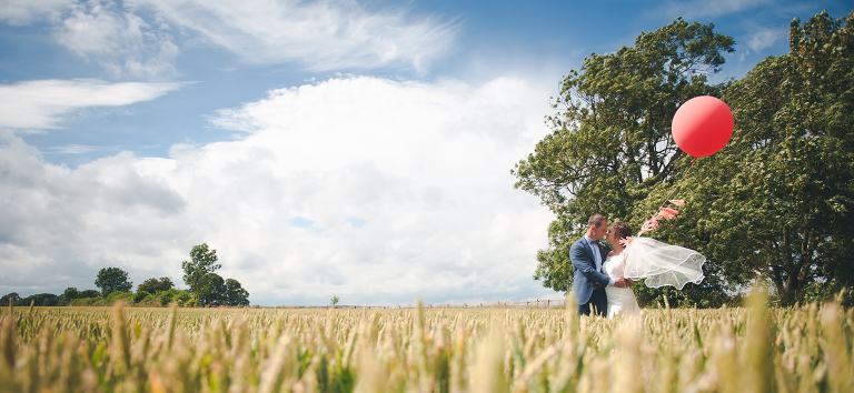 Image of newly married couple stood in a wheat field holding a red balloon