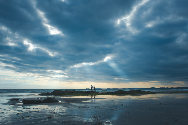 Engaged couple walking across druidstone beach with a dramatic sky and birds flying in the background