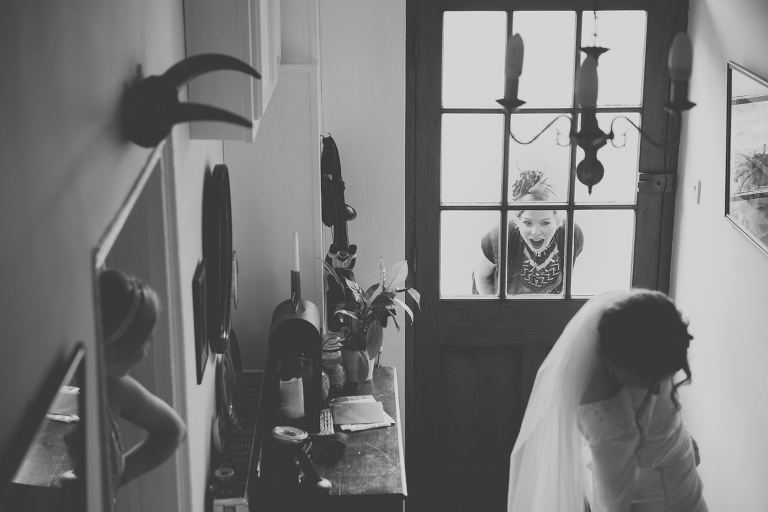 A reportage photograph which captures the brides friend reacting to seeing her for the first time ahead of her wedding on the family farm in a tipi in West Wales.