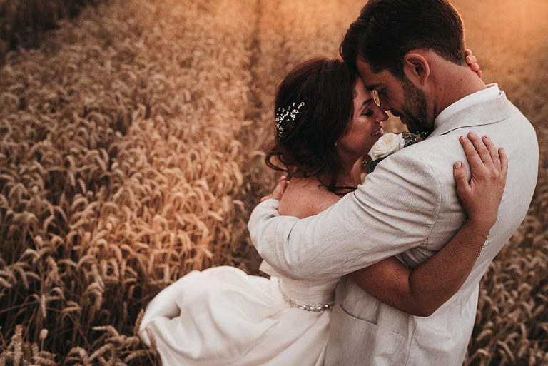 A bride and groom who's wearing a cream jacket and bow tie walk hand in hand through a wheat field.